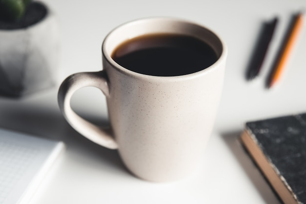 Schreibtisch tisch mit zubehör, kaffeetasse und blume.