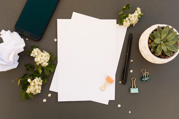 Schreibtisch, tisch verspotten mit smartphone, leer pappers, frühlingsblumen rahmen auf. büroarbeitstisch. kopieren sie platz.