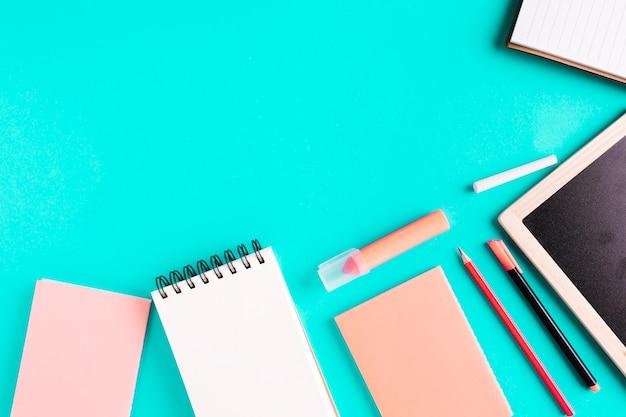 Schreibtisch und schulmaterial auf farbiger oberfläche