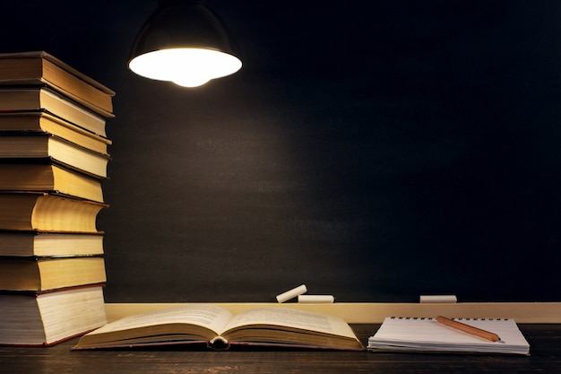 Schreibtisch vor dem hintergrund der kreidetafel, der bücher, des notizbuches und der stifte, im dunkeln unter dem licht einer lampe.