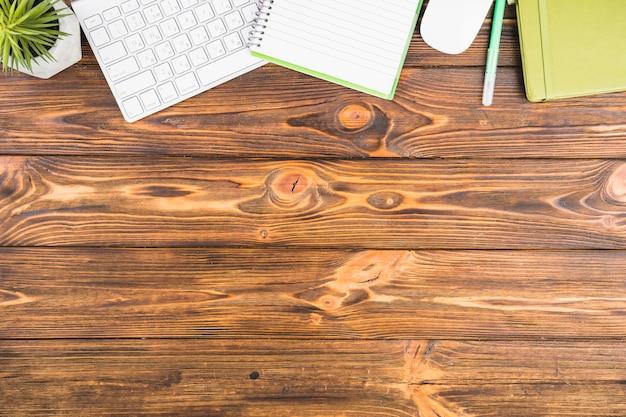 Schreibtischanordnung auf hölzernem hintergrund