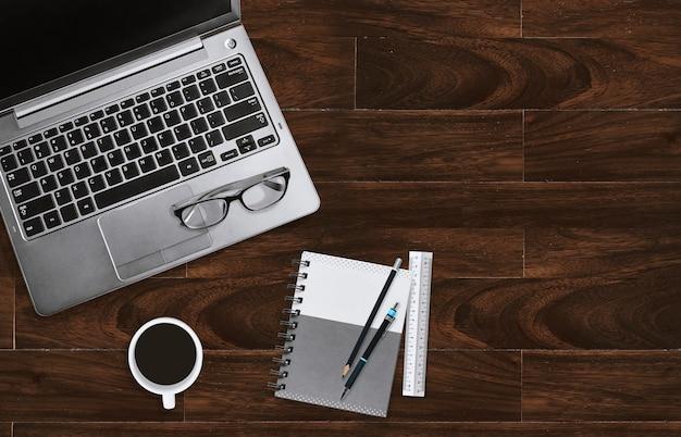 Schreibtischarbeitsplatz des homeofforts mit laptop mit brillen und notizbuch mit kopienraum.