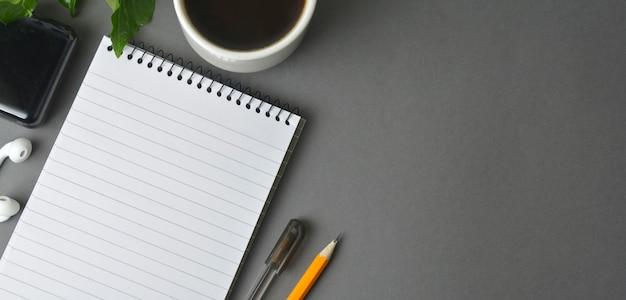 Schreibtischarbeitsplatz, grauer arbeitsplatz mit tasse kaffee, leeres notizbuch und anlage auf dunkler tabelle.