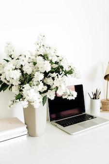 Schreibtischarbeitsplatz mit blumenstrauß, laptop und tischlampe