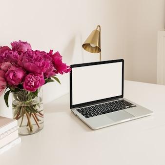 Schreibtischarbeitsplatz mit leerem kopierraum laptop-bildschirm. modernes stilvolles hauptinnendesign mit blumenstrauß der rosa pfingstrosen