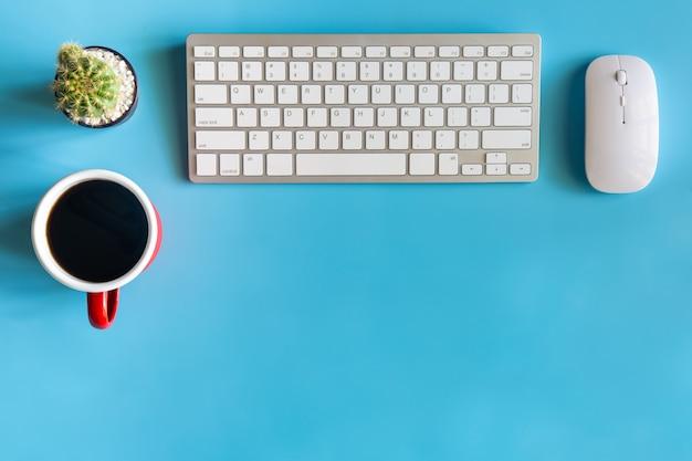 Schreibtischbüro mit tastatur, maus, kaffeetasse und kaktus
