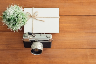 Schreibtischholztisch mit alter kamera und baum. draufsicht mit textfreiraum