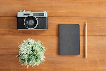 Schreibtischholztisch mit alter kamera und baum und notizbuch. draufsicht mit textfreiraum