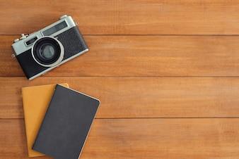Schreibtischholztisch mit alter kamera und notizbuch. draufsicht mit textfreiraum