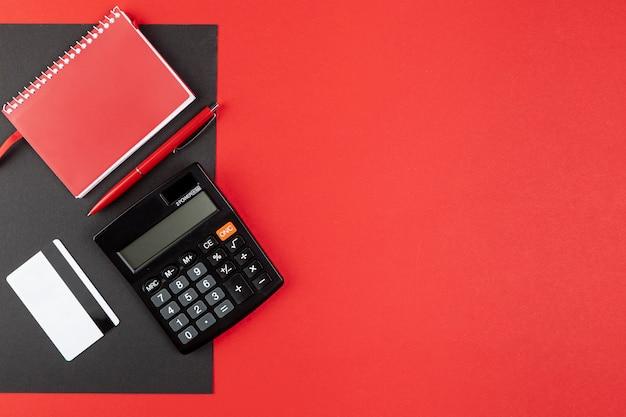 Schreibtischmaterial auf rotem hintergrund mit kopienraum