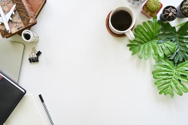 Schreibtischnotizblockpapier, laptop mit kaffeetassepflanze und kaktus mit draufsichtschreibtisch.