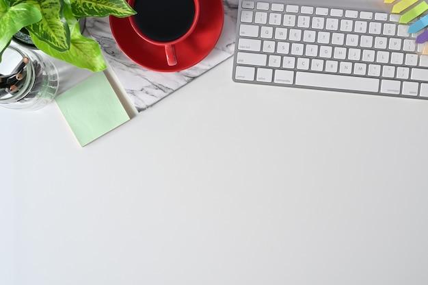 Schreibtischplatte mit computer-, kopfhörer-, bleistift-, kaffee- und pflanzendekoration.