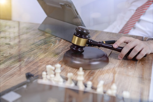 Schreibtischrichterhammer mit justizanwälten bei teambesprechung
