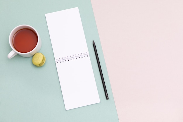 Schreibtischspott herauf schablone mit sauberem notizbuch, tastatur und tasse tee und makrone