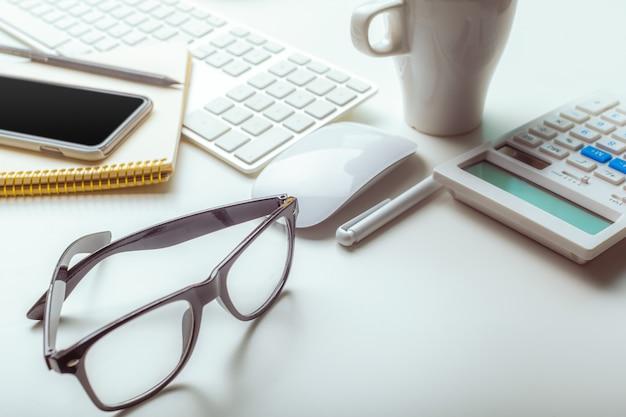 Schreibtischtabelle mit computertastatur, versorgungen, taschenrechner, stift, gläser