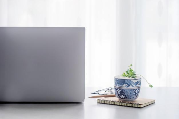 Schreibtischtabelle mit laptop-computer, zubehör mit kopienraum im büro.