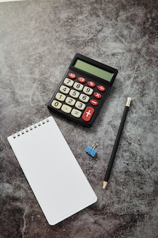 Schreibtischtabelle mit taschenrechner mit leerem anmerkungsbuch