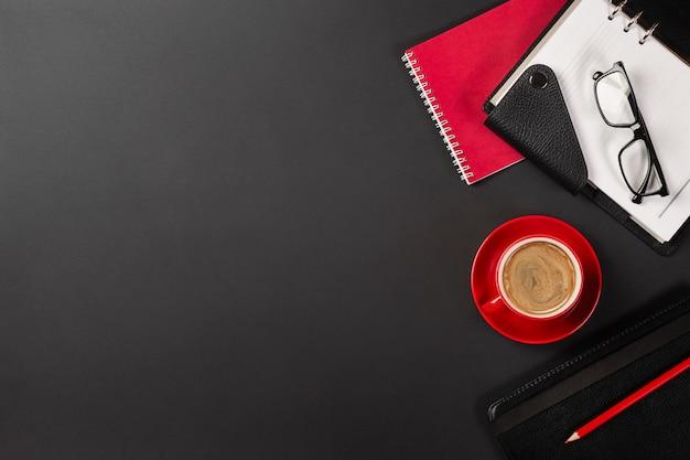 Schreibtischtabelle mit tasse kaffee und notizbüchern. draufsicht mit kopienraum
