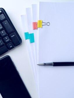 Schreibtischtisch mit computertastatur und zubehör. auf weißem hintergrund. draufsicht mit kopienraum. attrappe, lehrmodell, simulation