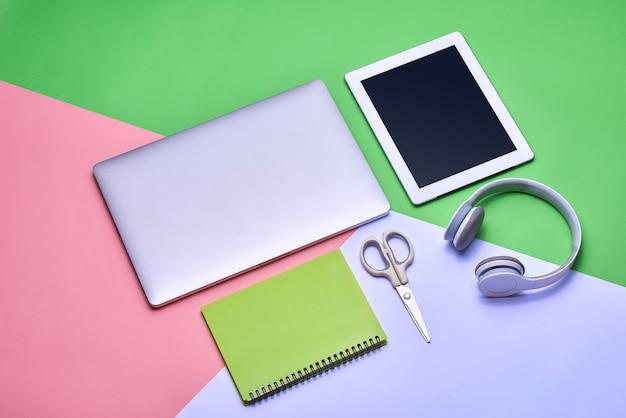 Schreibtischtisch mit laptop, kaffeetasse, kopfhörer und kamera auf farbtisch