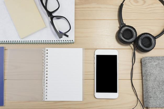 Schreibtischzubehör, notizbuch, kopfhörer, gläser auf holztisch.