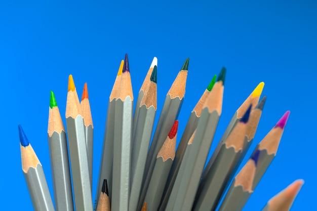 Schreibwaren der schule. satz einfache farbstifte auf blauem hintergrund. konzeptfoto der schülerausbildung