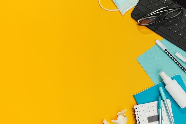 Schreibwaren-tastaturmasken und handdesinfektionsmittel gegen orangefarbenen tisch