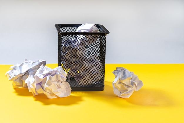 Schreibwarenkorb für stifte mit zerknitterten papierkugeln