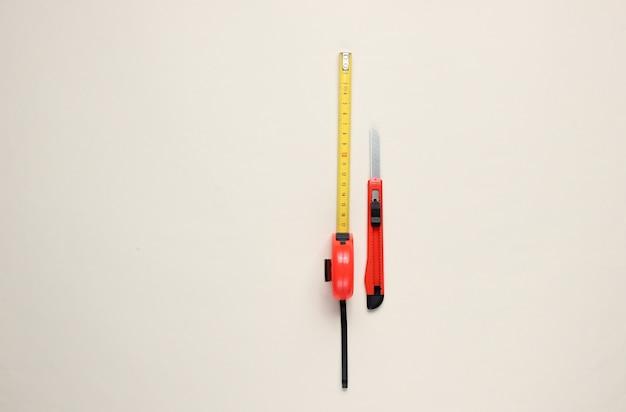 Schreibwarenmesser zum schneiden von papier und industriellem maßband auf beigem papier