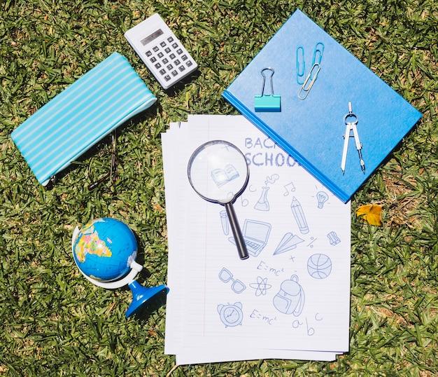 Schreibwarenschule eingestellt auf grünes gras