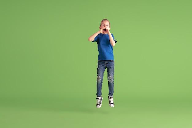 Schreien. fröhlicher junge, der auf grüner wand spielt und spaß hat. kaukasisches kind in hellem tuch sieht verspielt aus, lacht und lächelt. konzept der bildung, kindheit, emotionen, gesichtsausdruck.