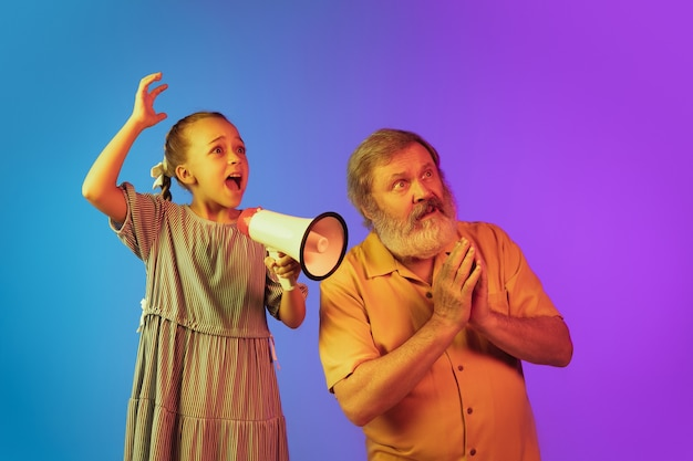 Schreien mit megaphon. älterer mann verbringt glückliche zeit mit enkelin im neon. fröhlicher älterer lebensstil, familie, kindheit, technologiekonzept, verkauf. viel spaß beim schreien mit megaphon. exemplar.
