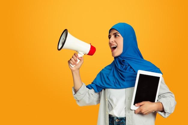 Schreien mit megaphon und tablet junge muslimische frau auf gelber wand