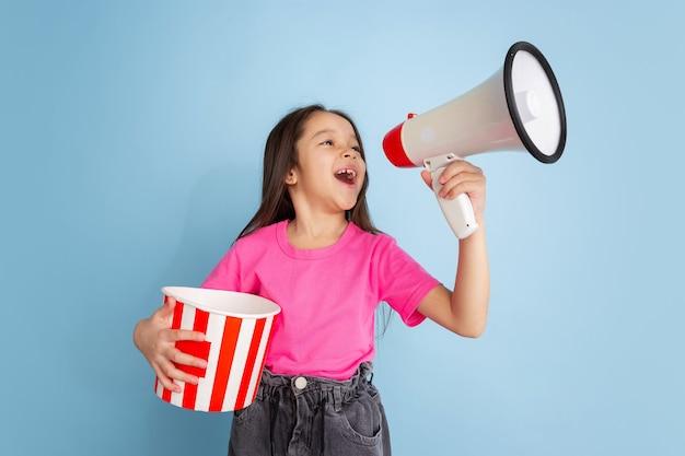 Schreien mit popcorn. kaukasisches porträt des kleinen mädchens auf blauer wand. schönes weibliches modell im rosa hemd. konzept der menschlichen emotionen, gesichtsausdruck, jugend, kindheit.