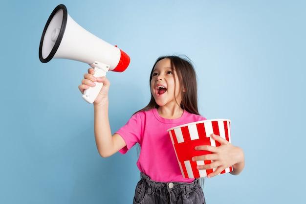 Schreien mit popcorn. kaukasisches porträt des kleinen mädchens auf blauer wand. schönes weibliches modell im rosa hemd.