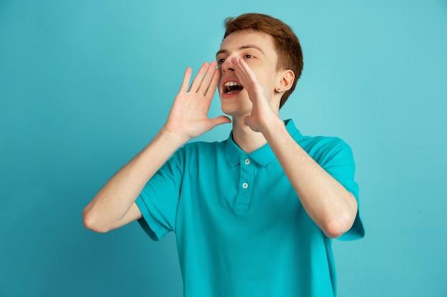 Schreien, rufen. das moderne porträt des kaukasischen jungen mannes lokalisiert auf blauer wand, monochrom. schönes männliches model. konzept der menschlichen emotionen, gesichtsausdruck, verkauf, anzeige, trendy.