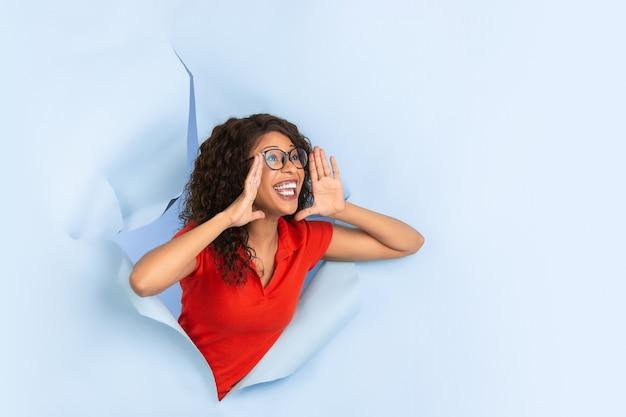 Schreien, rufen. fröhliche afroamerikanerin in zerrissenem blauem papierhintergrund, emotional, ausdrucksstark. aufbruch, durchbruch. konzept der menschlichen emotionen, gesichtsausdruck, verkauf, anzeige.