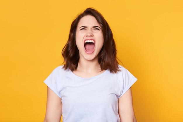 Schreiende emotionale verärgerte frau wirft isoliert über gelbem studio auf