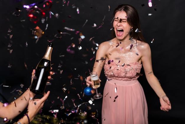 Schreiende frau im abendkleid mit glas- und verzierungsball nahe händen mit flasche