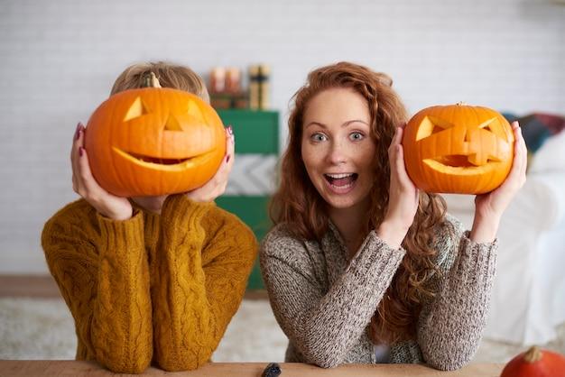 Schreiende frauen, die halloween-kürbisse zeigen