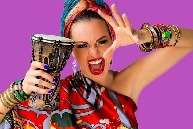 Schreiende junge attraktive sängerin im afrikanischen stil mit trommel an bunter wand
