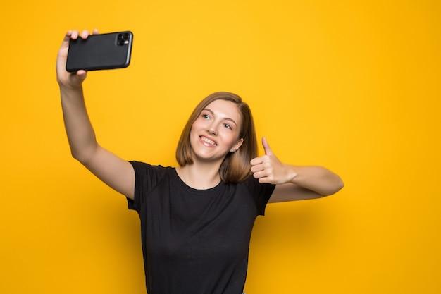 Schreiende junge frau, die ein selfie-foto auf gelb macht