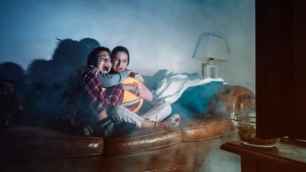 Schreiende mädchen, die horrorfilm aufpassen