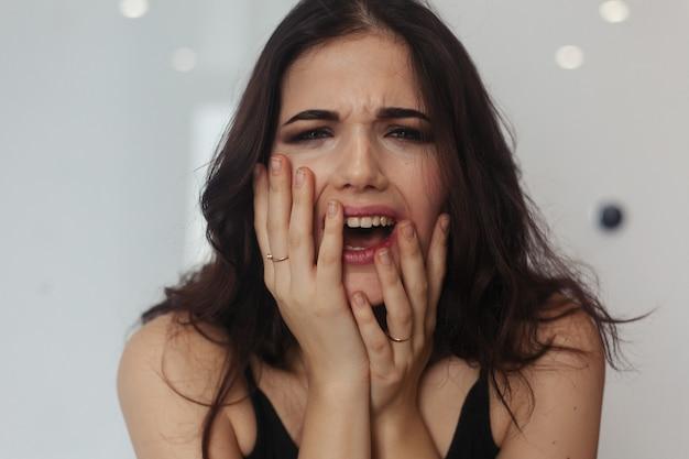 Schreiende wütende frau, die zu hause auf der couch sitzt. negative gedanken. arme gestresste frau, die auf dem badezimmer sitzt porträt einer frustrierten wütenden frau, die laut schreit