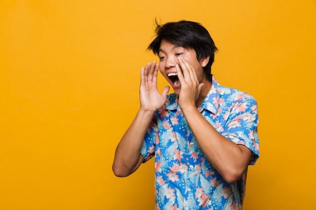 Schreiender emotionaler junger asiatischer mann, der isoliert über gelbem raum aufwirft.