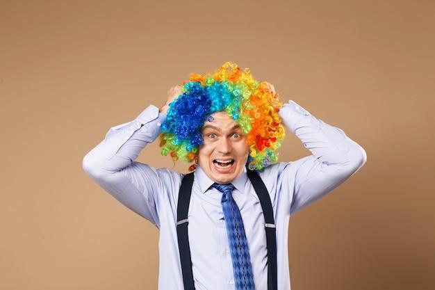 Schreiender geschäftsmann mit großer bunter perücke. nahaufnahmeporträt des geschäftsmannes in der clownperücke. unternehmenskonzept