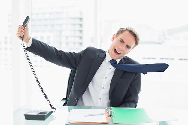 Schreiender geschäftsmann, wie er telefon im büro aushält