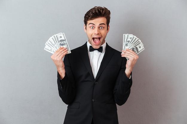 Schreiender gutaussehender mann, der geld hält.