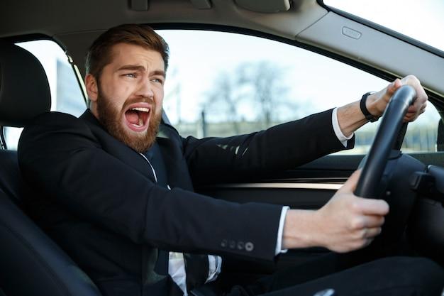 Schreiender junger geschäftsmann, der während der fahrt in einen autounfall gerät