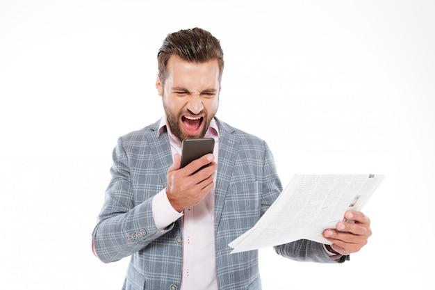 Schreiender junger mann, der gazette hält und per telefon spricht.